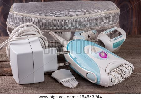 electric epilator with a bag on an old wooden background. Hair removal device
