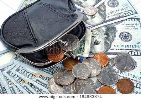 American dollars in black purse and coins on a white background. Close-up.