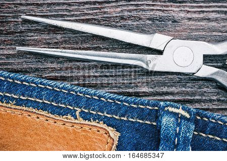 Blue jeans stitched edge and long nose pliers on dark wood. Everyday home repair background. Macro view