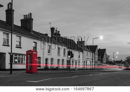 Village street with red telephone box and passing traffic captured as light trails on a long exposure