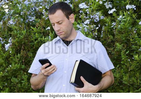 Distractions from God's Word. Bible or cell phone? Man choosing smart phone over his Bible.