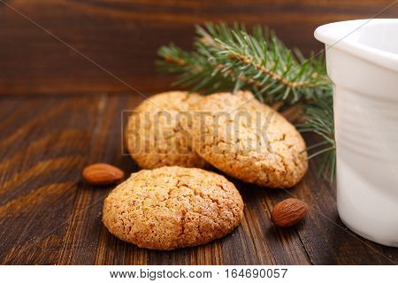 Almond cookie on a brown wooden background the branches of spruce