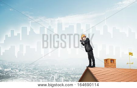 Young businessman in suit and helmet on roof edge in search of something new. Mixed media
