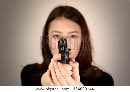 Close up young woman pointing a gun at the camera