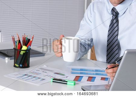 Handsome businessman having tea or coffee in office.
