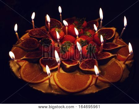Processed with VSCO with h3 preset, a cake with candles and fruits, with black background