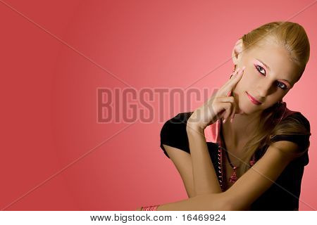 young beautiful blond girl on pink background with space
