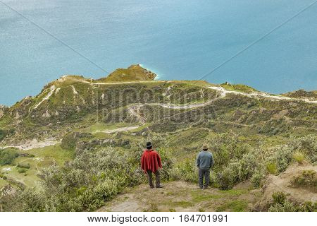 Two adult indian watching the view at Quilotoa lagoon Ecuador