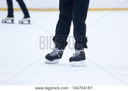 the legs of a man skating on an ice rink.