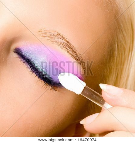 close-up of young beautiful girl make her make-up with brush