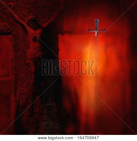 Small and big metal sculpture of the crucified Christ on the cross in a dark red background of the burning