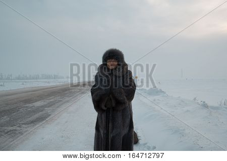 Portrait of senior woman fur coat and hat standing in cold winter snow covered road, telephoto, wide angle