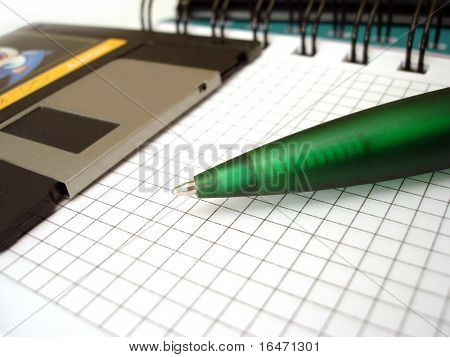 close-up of pen and diskette on notebook