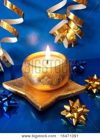 golden candle and ribbon on blue background