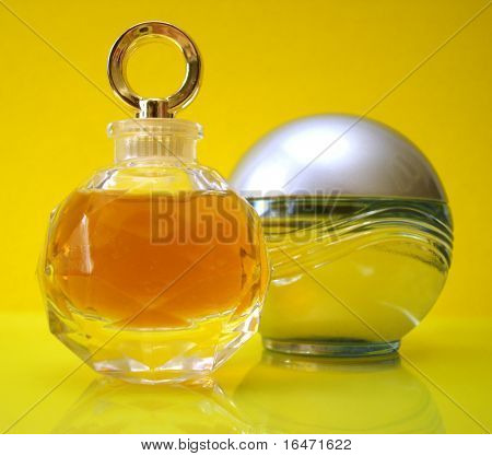 bottles of perfume over yellow background