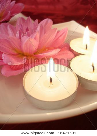 Spa essentials (candles and pink flowers on water)
