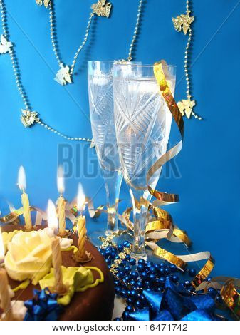 celebratory table (cake and candles, two glasses with champagne, gift boxes) on blue