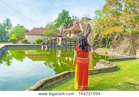 The young tourist at the bank of the pond of Isurumuniya Viharaya wathes the Rock Temple in shade of trees Anuradhapura Sri Lanka.