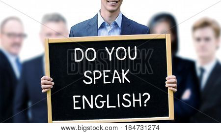 young businessman holding a sign with the words Do You Speak English and group of people behind him