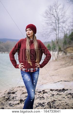 portrait of beautiful young woman in burgundy hat and sweater against the background of the lake