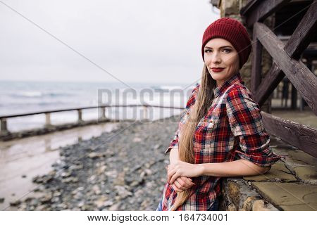 portrait of beautiful young woman in burgundy hat and plaid shirt on the shore of the stormy sea