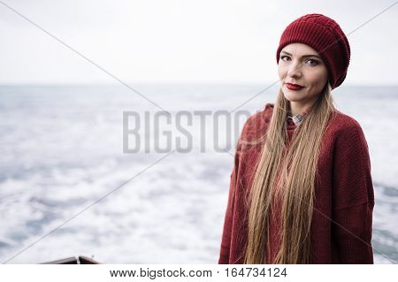 portrait of beautiful young woman in burgundy hat and sweater against the backdrop of stormy sea