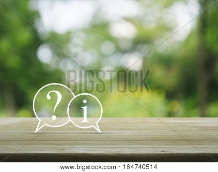 Question mark and information chat icon on wooden table over blur green tree background Customer support concept