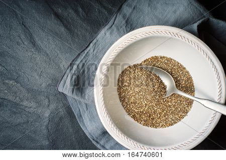Chia seeds in the white plate with spoon on the dark stone table top view