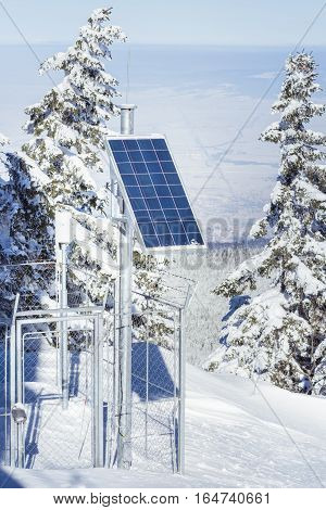 Solar cells on top of mountain in winter season surrounded by snow