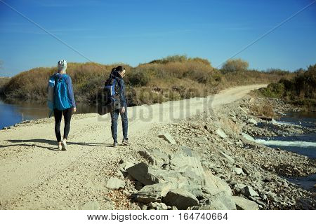Two Young Ladies With Backpacks Walking At Sunny Day  Photo