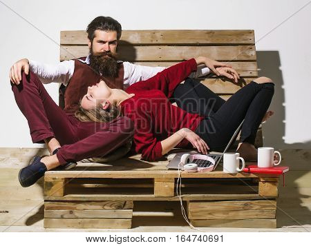 Young couple spend time together on wooden pallet sofa. Handsome man bearded hipster with beard uses laptop computer. Pretty girl or beautiful woman reads book