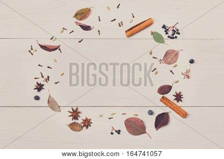 Various spices for mulled wine background. Round frame made of herbs and condiments as cinnamon, cardamom, clove, anise and sloe. Top view of cooking ingredients on white wood, flat lay, copy space