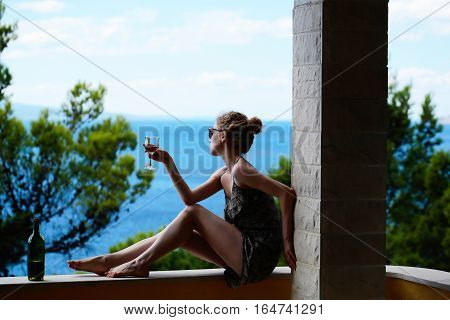 Cute female holding glass with white wine in hand with open bottle sitting on railing of balcony and looking at sea on natural background.