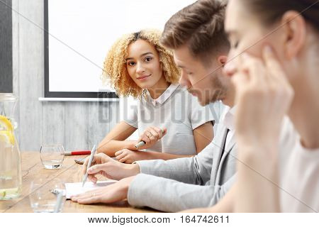 Meeting of the company. Young accountant reads documents. Team of workers preparing a presentation
