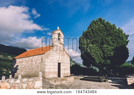 Lonely tree and stone church with bell tower at Gradiste monastery under evening lights near Buljarica, Montenegro.