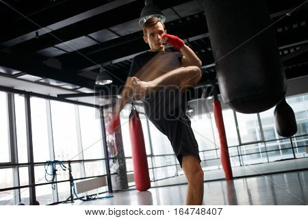 Training of young boy with boxing bag in sports gym