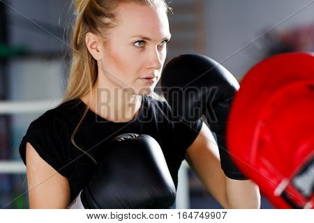Woman engaged in boxing with trainer in gym