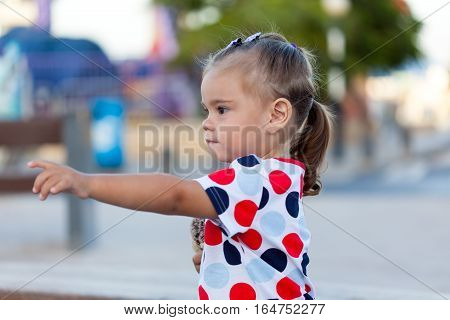 Little child girl outside pointing to something