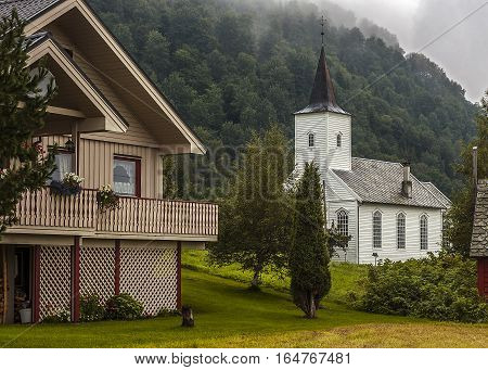 Norway early in the morning in a small village on the banks of Neroyfiord fog in the mountains . Wooden house and church - Kirk.