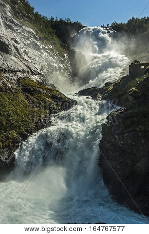 Norway Flam. Kjosfossen famous waterfall on the banks of which stands a beautiful Hyuldra - a mythical character.