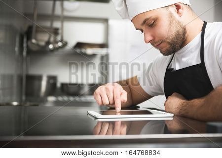 Chef In The Kitchen Using Tablet