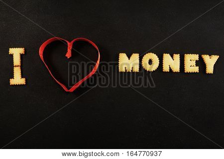 Text I heart money on black with red ribbon