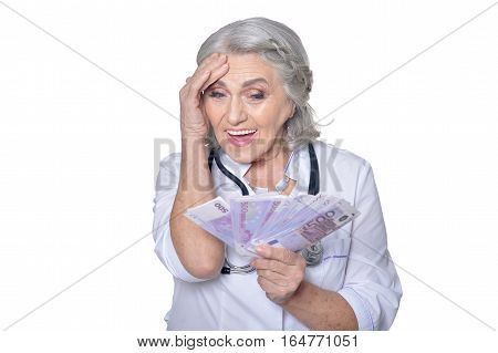 mature female doctor with money, posing against white