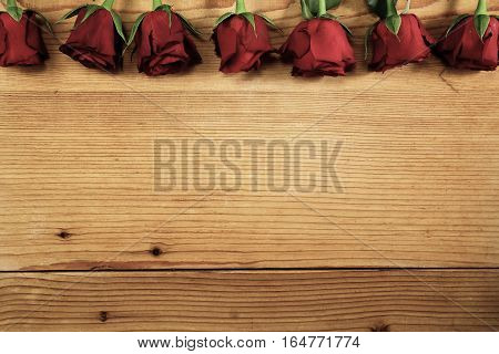 Red roses on the textured wood with copy space