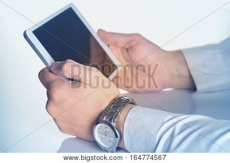 Tablet computer in male hands stained in blue. The original size of the tablet PC is changed.
