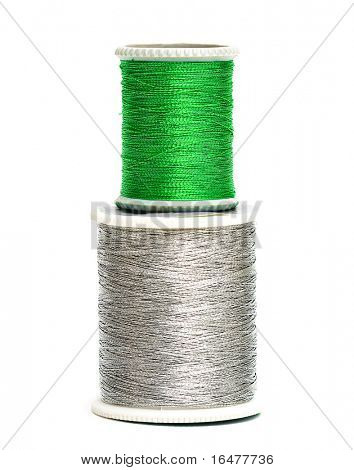 green and silver spools of threads