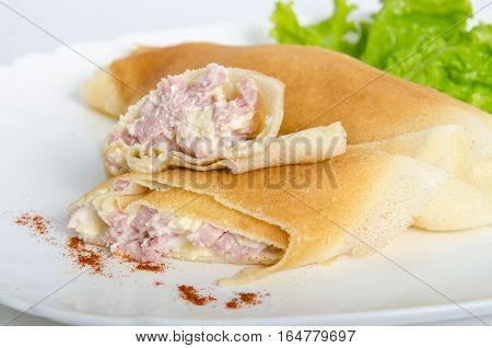 portion of rolled pancakes or crepes cut in half stuffed with ham and cheese on oval dishes served with green salad