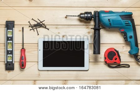 Set of construction tools to repair on a wooden table: white tablet, drill, hammer, pliers, self-tapping screws, roulette, level, drawing, screwdriver. Top view Workspace joiner