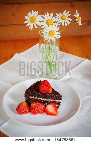 Chocolate cake with fresh strawberry and chamomile
