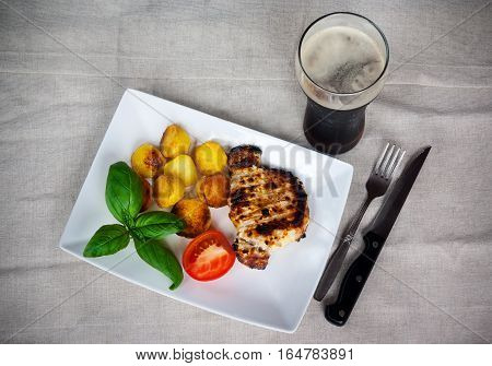 Grilled pork covered by sauce with roasted potato and glass of beer